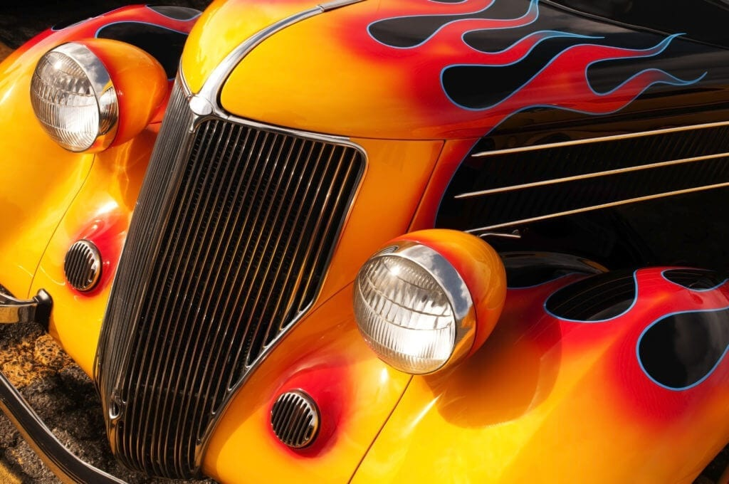 Classic hot rod with red flames on black paint.